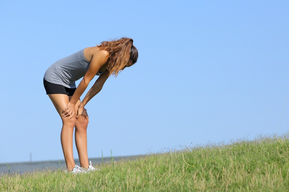 Fitness woman tired resting on the grass with the sky in the background