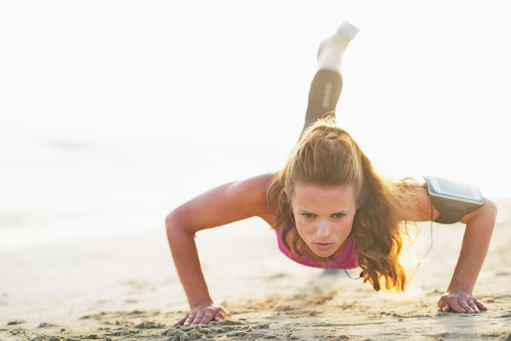 Female athlete doing push ups on beach