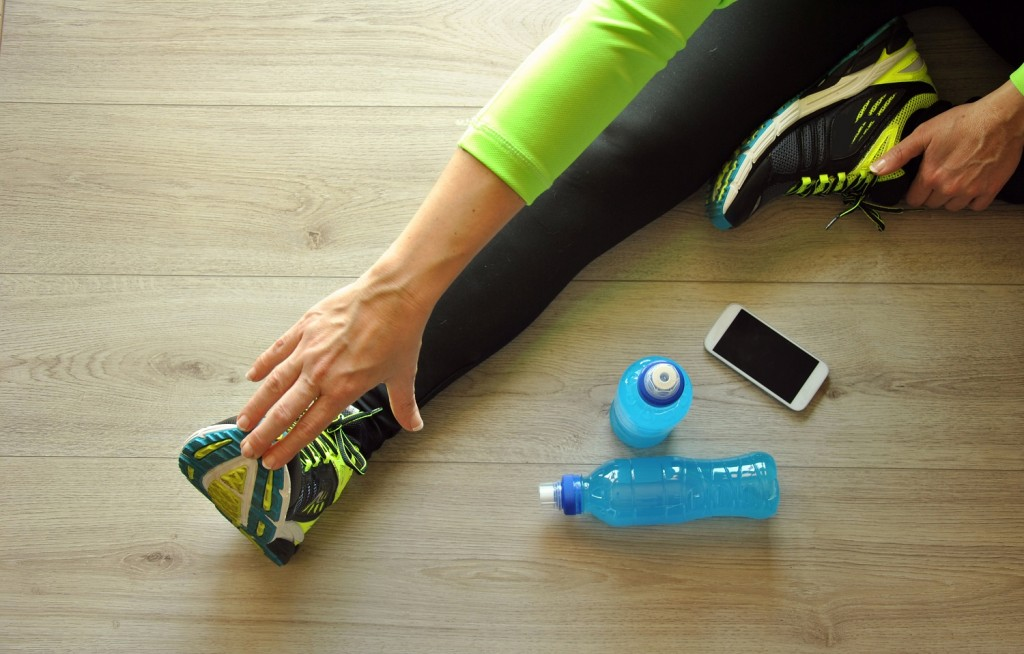 runner legs stretched on wooden floor with drink