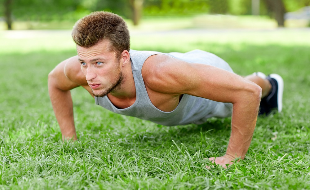 young man doing wide grip push up on grass in summer park